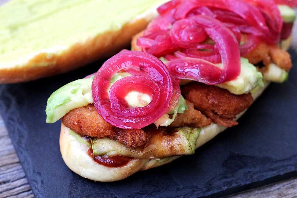 Sanduíche de camarão empanado, abacate, abobrinha grelhada, picles de cebola