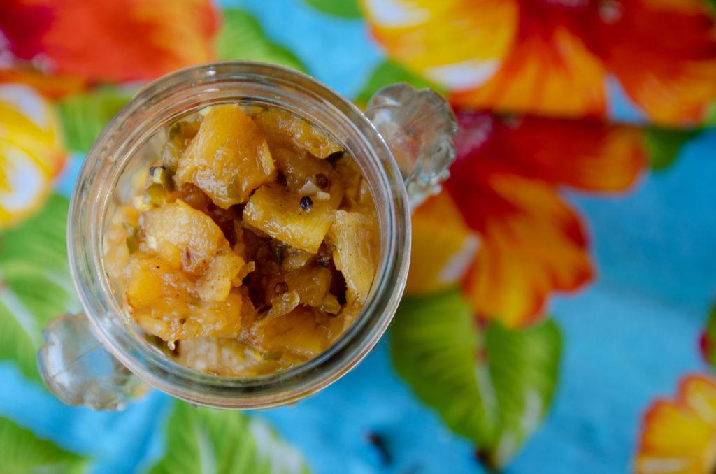 chutney de abacaxi em vasilhame de vidro sobre toalha florida visto de cima