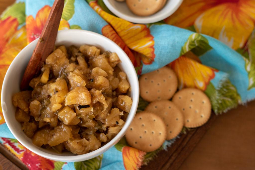 visto de cima, um bowl branco com chutney de abacaxi em seu interior, rodeado de bolachas salgadas